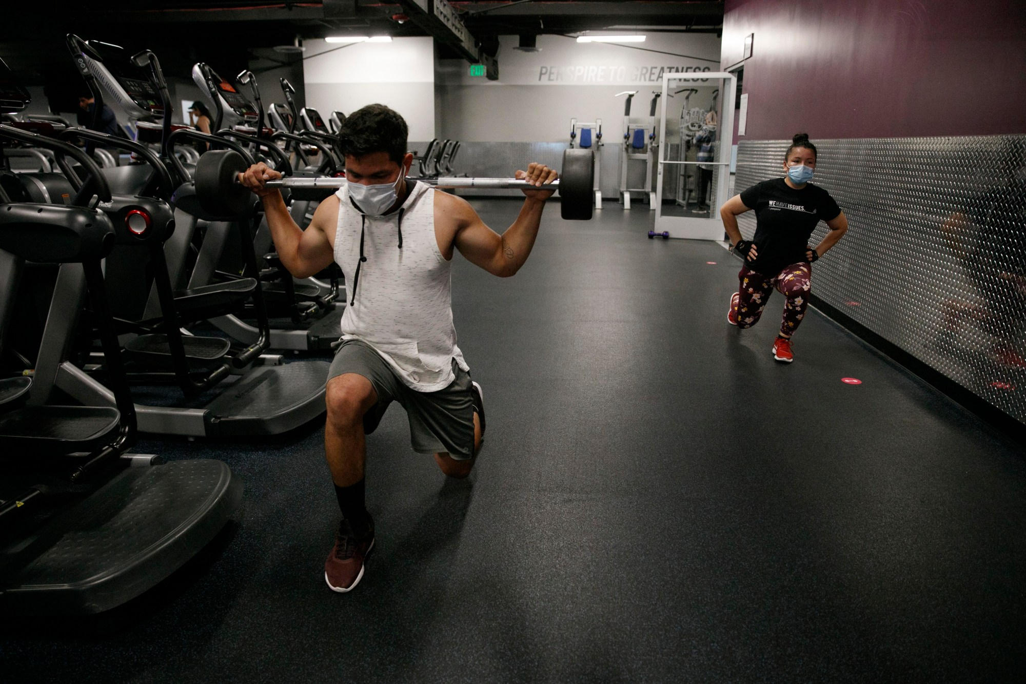 people wear masks while exercising at a gym in Los Angeles on June 26, 2020. (AP Photo/Jae C. Hong)