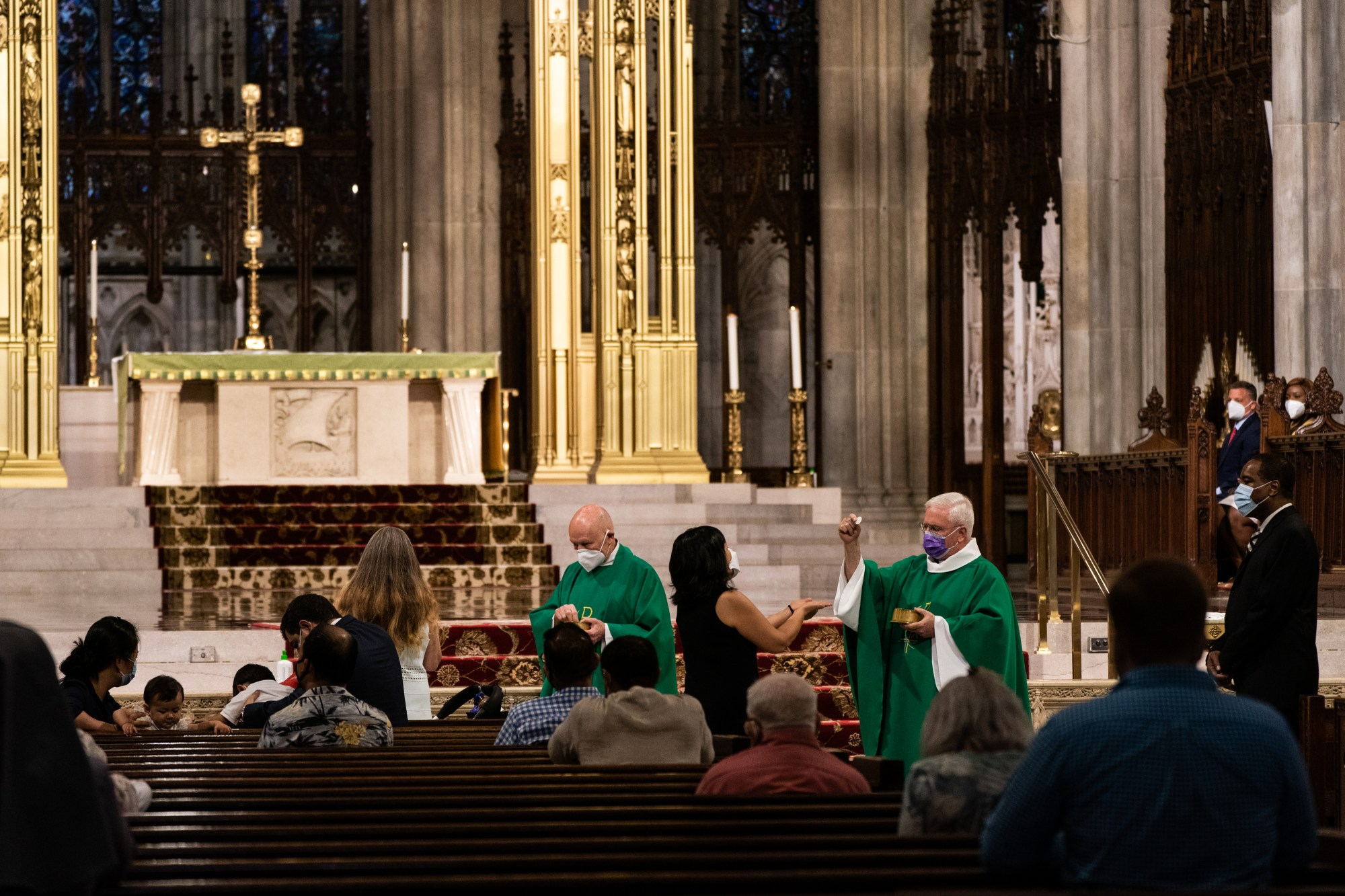 Priests wearing protective masks give communion at St. Patrick's Cathedral on June 28, 2020 in New York City. (Jeenah Moon/Getty Images)