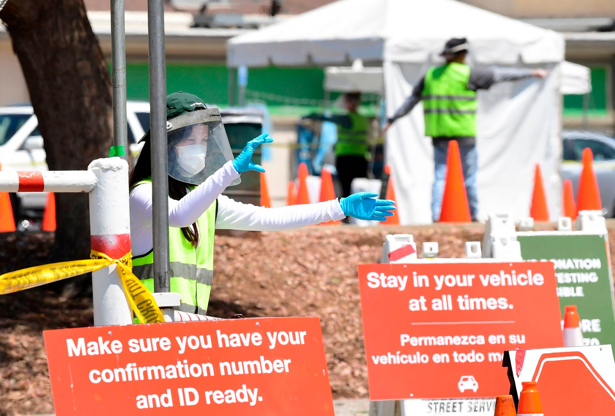 COVID-19 test site volunteers wearing personal protective equipment assist drivers arriving at a coronavirus test site in Los Angeles on July 10, 2020. (Frederic J. Brown / AFP / Getty Images)