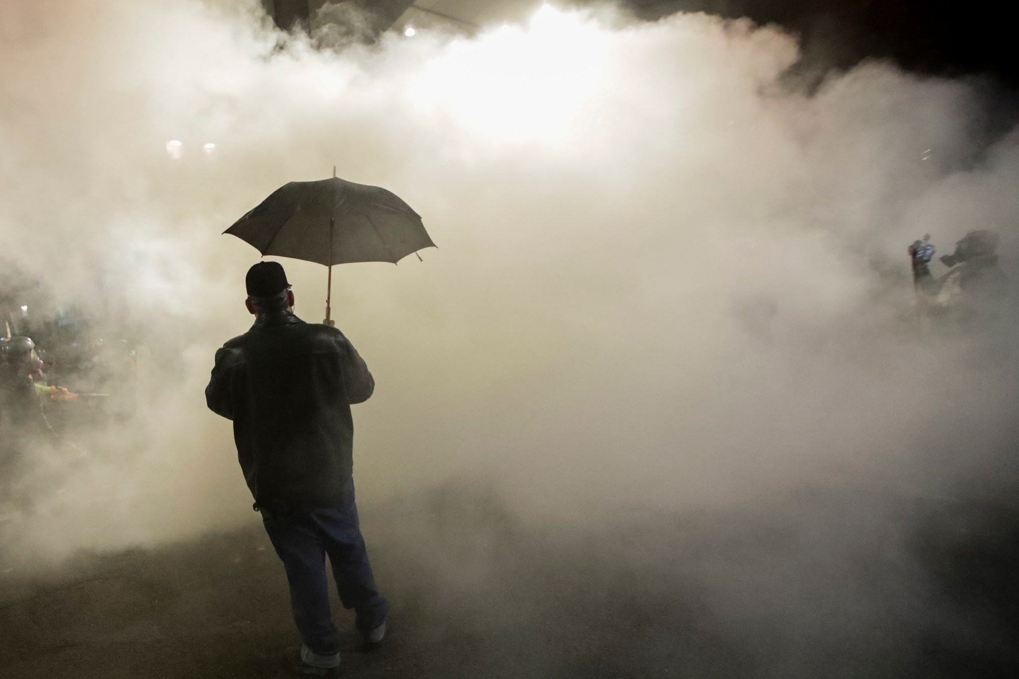 A protester carries an umbrella as federal police officers deploy tear gas during a protest at the Mark O. Hatfield U.S. Courthouse in Portland, Oregon on July 25, 2020. (Marcio Jose Sanchez/Associated Press)