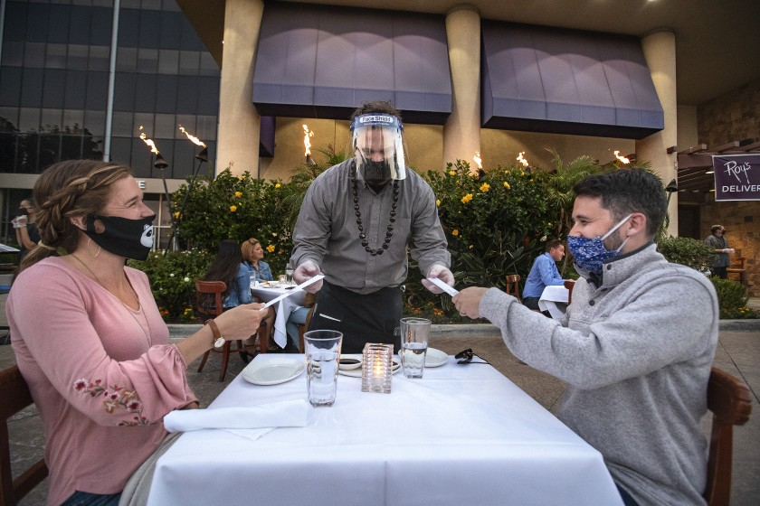 Jason Ruckart, managing partner at Roy's restaurant in Woodland Hills, hands chopsticks to Nicole Lehning and her husband, Kyle, as they dine outdoors in what was previously the valet parking area.(Mel Melcon / Los Angeles Times)
