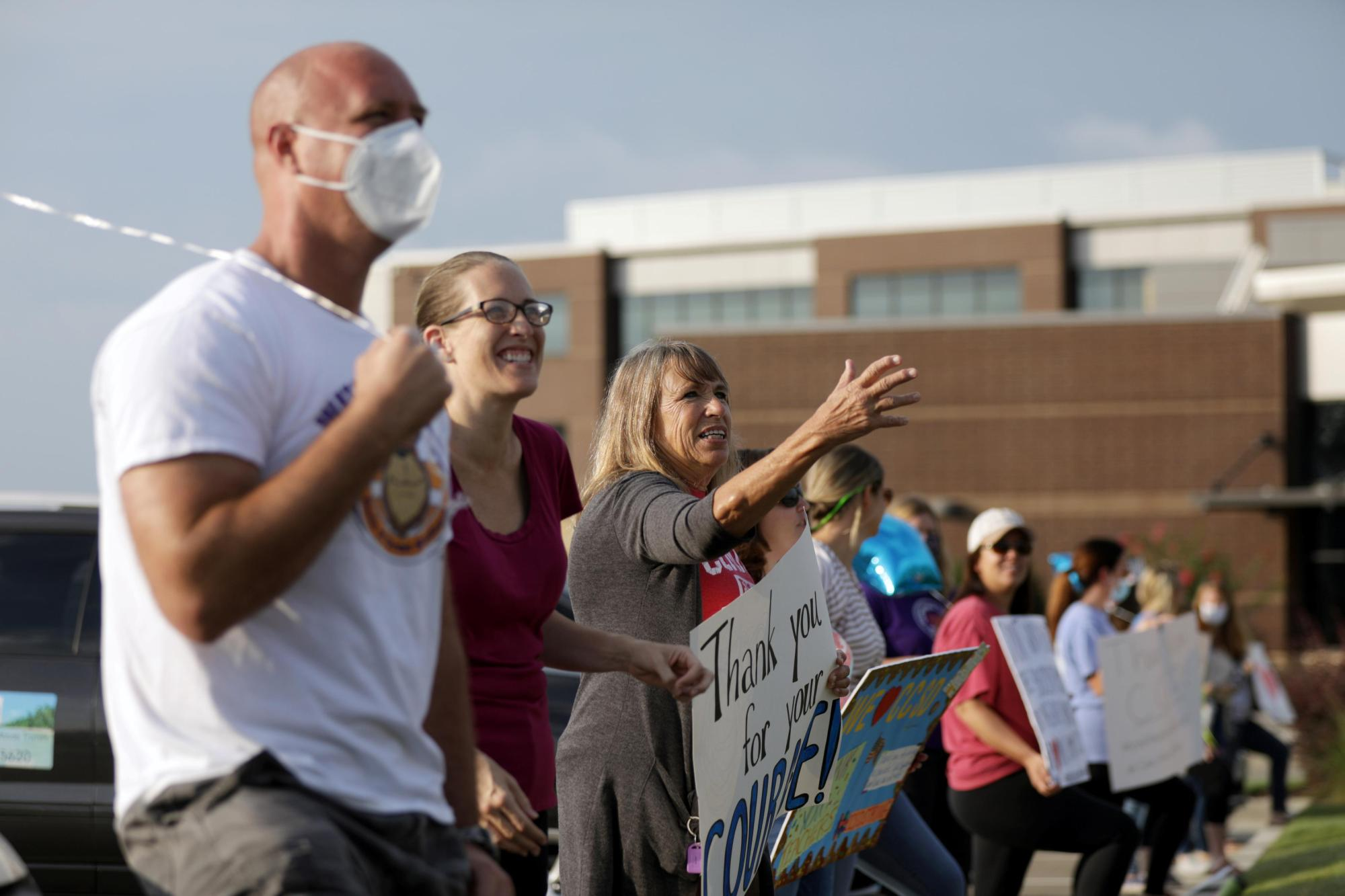 Supporters of the Cherokee County School District's decision to reopen schools cheer on faculty arriving to the district's headquarters in Canton, Georgia. (Dustin Chambers/Reuters)