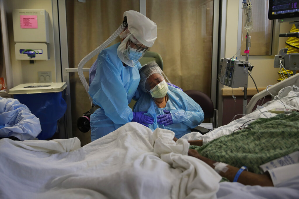 In this July 31, 2020, file photo, Romelia Navarro, right, is comforted by nurse Michele Younkin, left, as she weeps while sitting at the bedside of her dying husband, Antonio Navarro, in St. Jude Medical Center's COVID-19 unit in Fullerton. (AP Photo/Jae C. Hong, File)