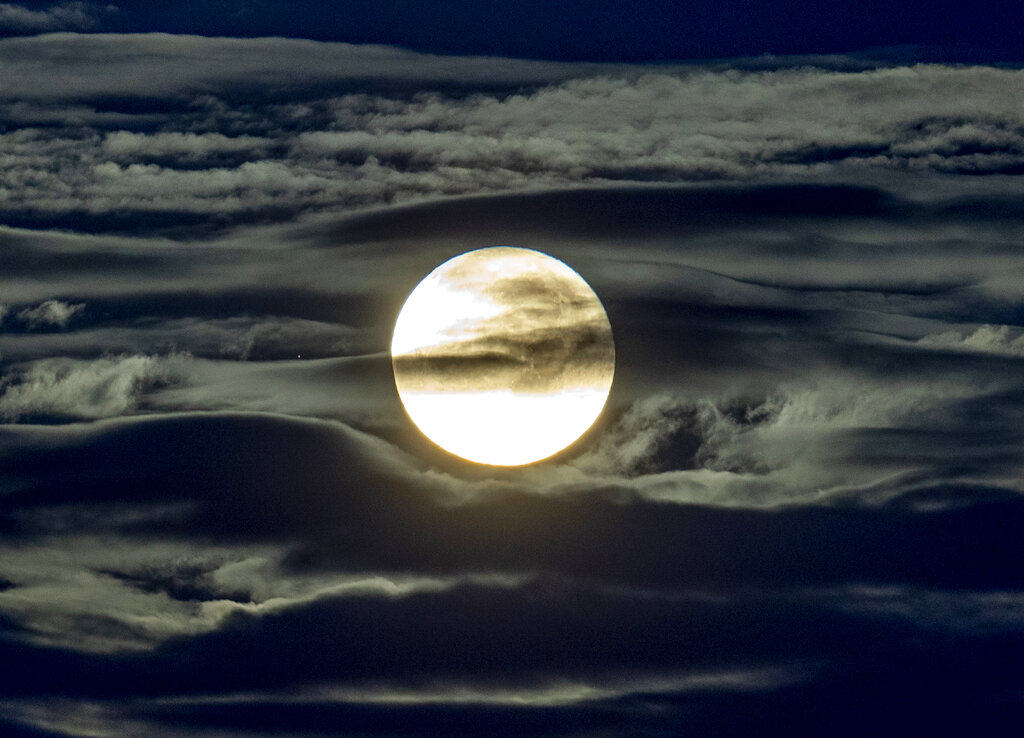 In this Sept. 2, 2020 file photo, the full moon shines surrounded by clouds in the outskirts of Frankfurt, Germany. (AP Photo/Michael Probst, File)