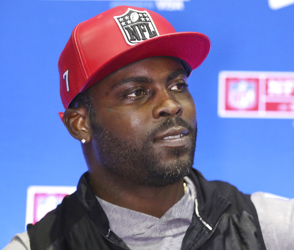 Former Falcons and Eagles quarterback Michael Vick signs autographs in the NFL Shop at the Super Bowl Experience in Atlanta in Jan. 31, 2019 file photo. (Curtis Compton/Atlanta Journal-Constitution via AP, File)/Atlanta Journal-Constitution via AP)