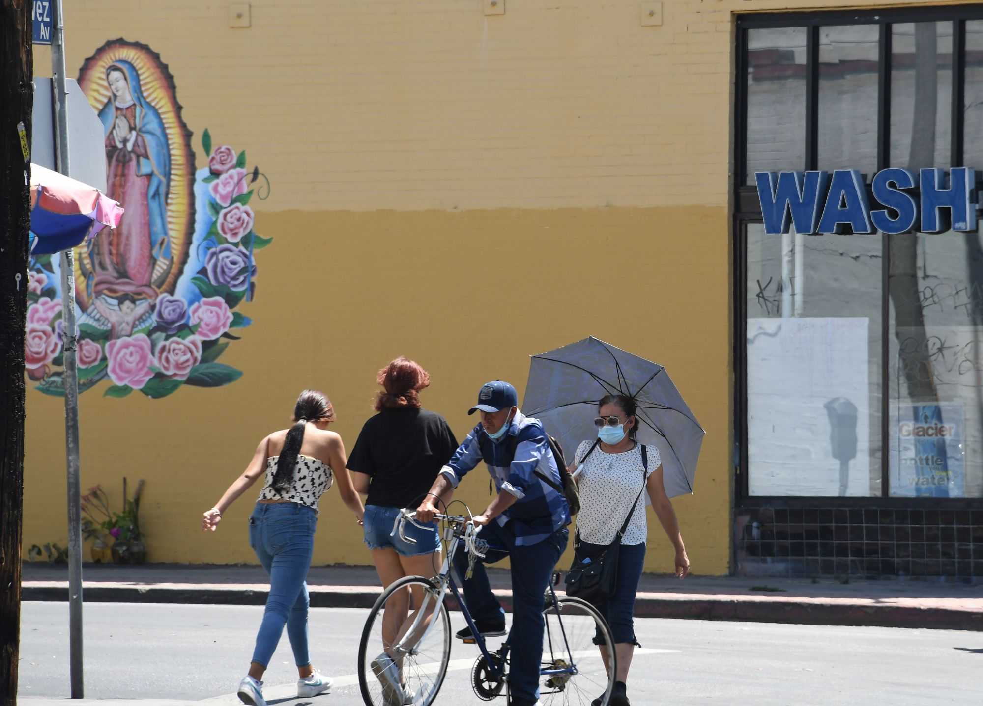 People cross the street in the largely Latino neighborhood of East Los Angeles, August 7, 2020 in Los Angeles, California during the coronavirus pandemic. (Robyn Beck / AFP) (Photo by ROBYN BECK/AFP via Getty Images)