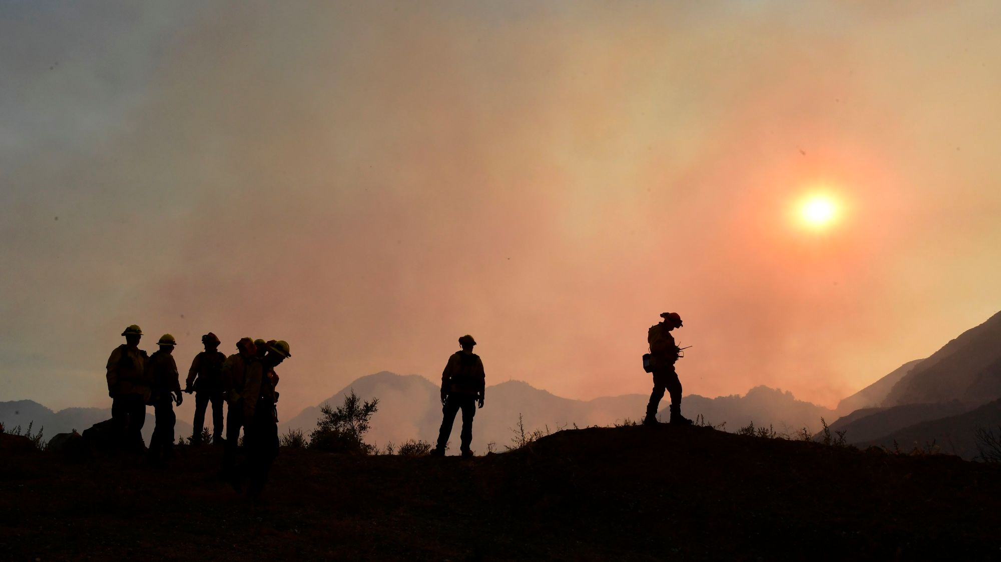 Firefighters position themselves on a ridge overlooking smoldering fires from the Bobcat Fire in a valley below in the Angeles National Forest on Sept. 23, 2020 in Los Angeles. (FREDERIC J. BROWN/AFP via Getty Images)