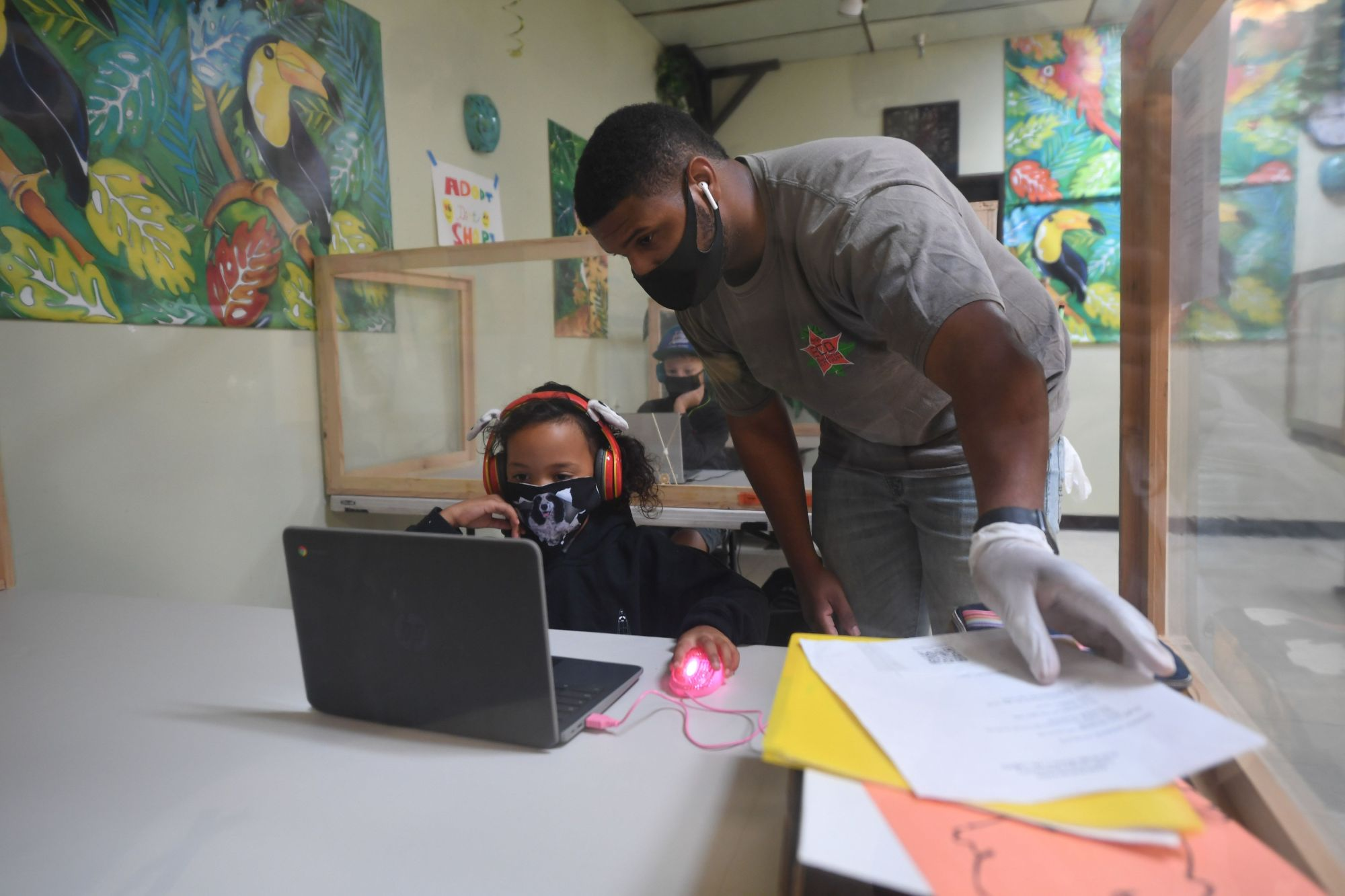 An instructor helps a student with her online school lesson at a desk separated from others by plastic barriers at STAR Eco Station Tutoring & Enrichment Center on Sept. 10, 2020 in Culver City, California. (ROBYN BECK/AFP via Getty Images)