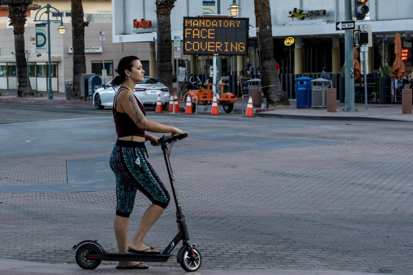 A woman travels on a scooter in downtown Palm Springs in Riverside County on July 16. (Gina Ferazzi/Los Angeles Times)