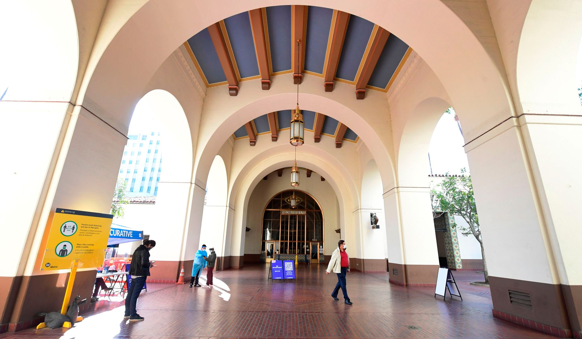 Testing Center Specialists fully dressed in personal protective equipment assist people arriving for a coronavirus test at Union Station in Los Angeles on Nov. 13, 2020. (FREDERIC J. BROWN/AFP via Getty Images)