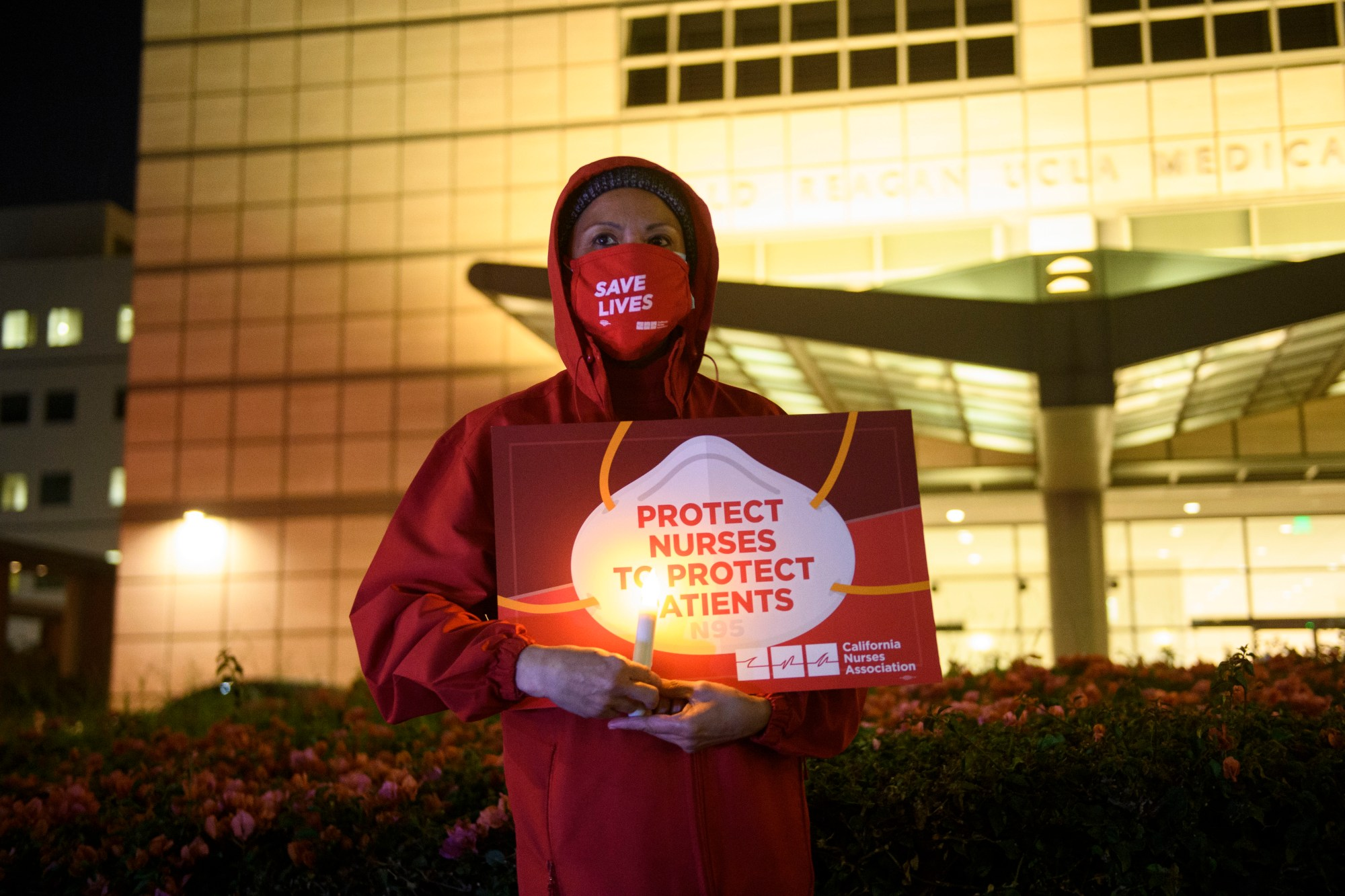A nurse holds a candle during a vigil for health care workers who died from COVID-19 organized by California Nurses United outside of UCLA Medical Center in Los Angeles. (PATRICK T. FALLON/AFP via Getty Images)
