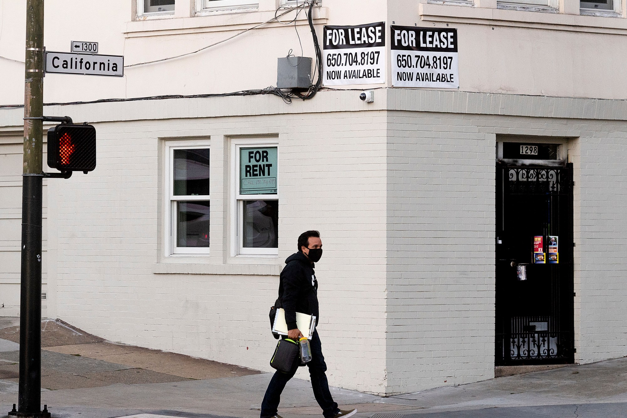 A pedestrian passes under for rent and for lease signs in San Francisco on Oct. 21, 2020. (Noah Berger/Associated Press)