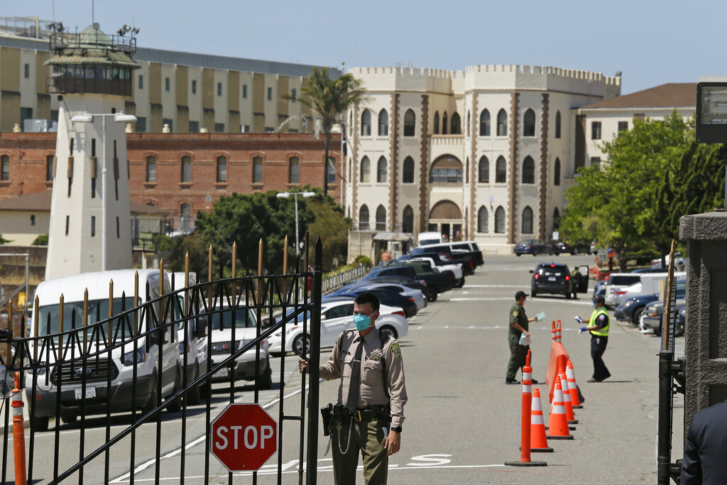 In this July 9, 2020, file photo, a correctional officer closes the main gate at San Quentin State Prison in San Quentin. (AP Photo/Eric Risberg, File)