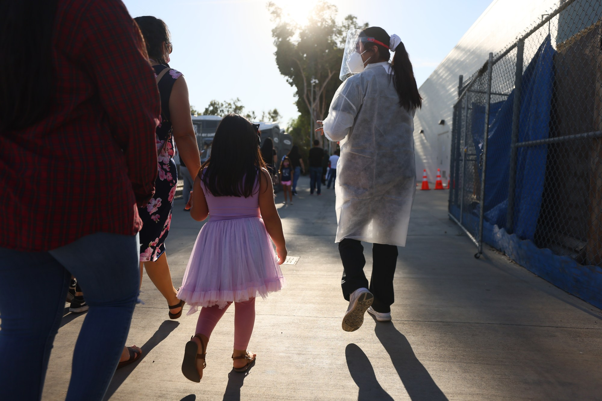 A USC research team member walks with a family after recruiting them to participate in a rapid antigen testing program at a walk-up COVID-19 testing site on Dec. 2, 2020, in San Fernando. (Mario Tama/Getty Images)