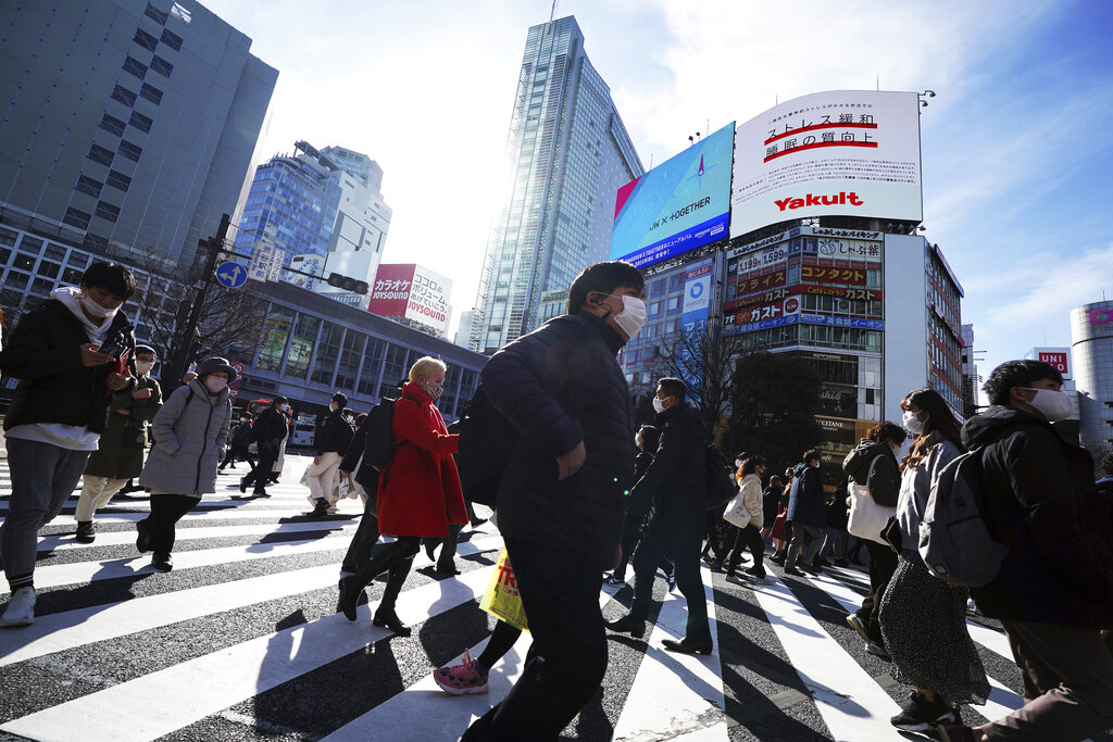 People wearing protective masks to help curb the spread of the coronavirus walk along pedestrian crossings Monday, Jan. 25, 2021 in Tokyo. (AP Photo/Eugene Hoshiko)