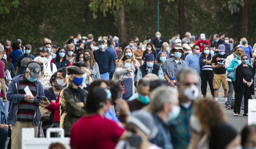 Healthcare workers wait in line to receive the COVID-19 vaccine at the Disneyland Resort in Anaheim.(Allen J. Schaben / Los Angeles Times)