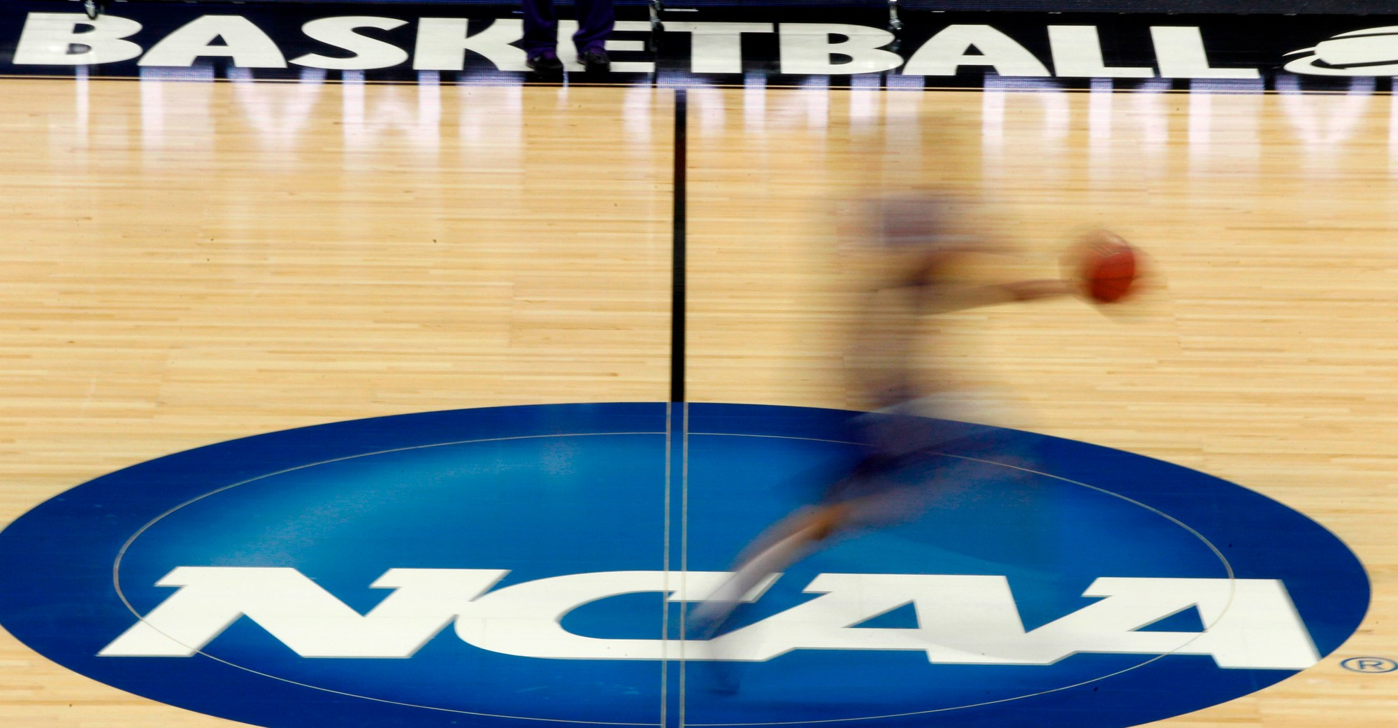 In this March 14, 2012, file photo, a player runs across the NCAA logo during practice in Pittsburgh before an NCAA tournament college basketball game. (AP Photo/Keith Srakocic, File)
