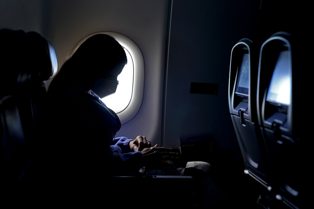 In this Wednesday, Feb. 3, 2021, file photo, a passenger wears a face mask she travels on a Delta Air Lines flight after taking off from Hartsfield-Jackson International Airport in Atlanta. (AP Photo/Charlie Riedel, File)