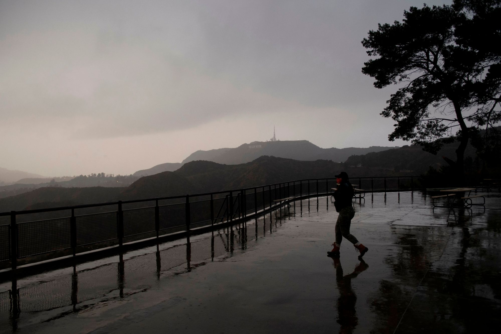 A person wears a face mask while walking to take pictures from a viewing area overlooking the Hollywood sign shrouded by clouds during heavy rains as seen from the Griffith Observatory on December 28, 2020 in Los Angeles, California. (Patrick T. Fallon/AFP via Getty Images)