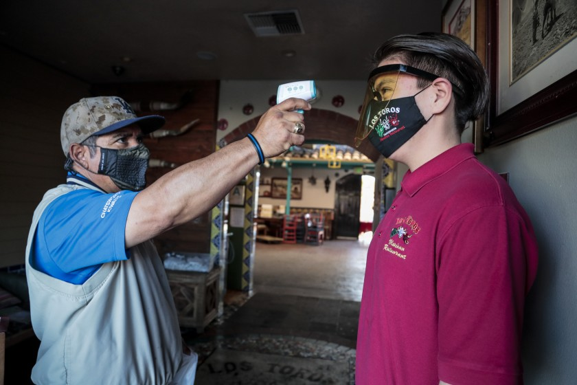 Nicolas Montaño, owner of Los Toros Mexican Restaurant in Chatsworth, scans the temperature of Diego Almendor. Montaño scans workers before every shift, hoping to keep them safe and avoid having to pay sick leave.(Robert Gauthier / Los Angeles Times)