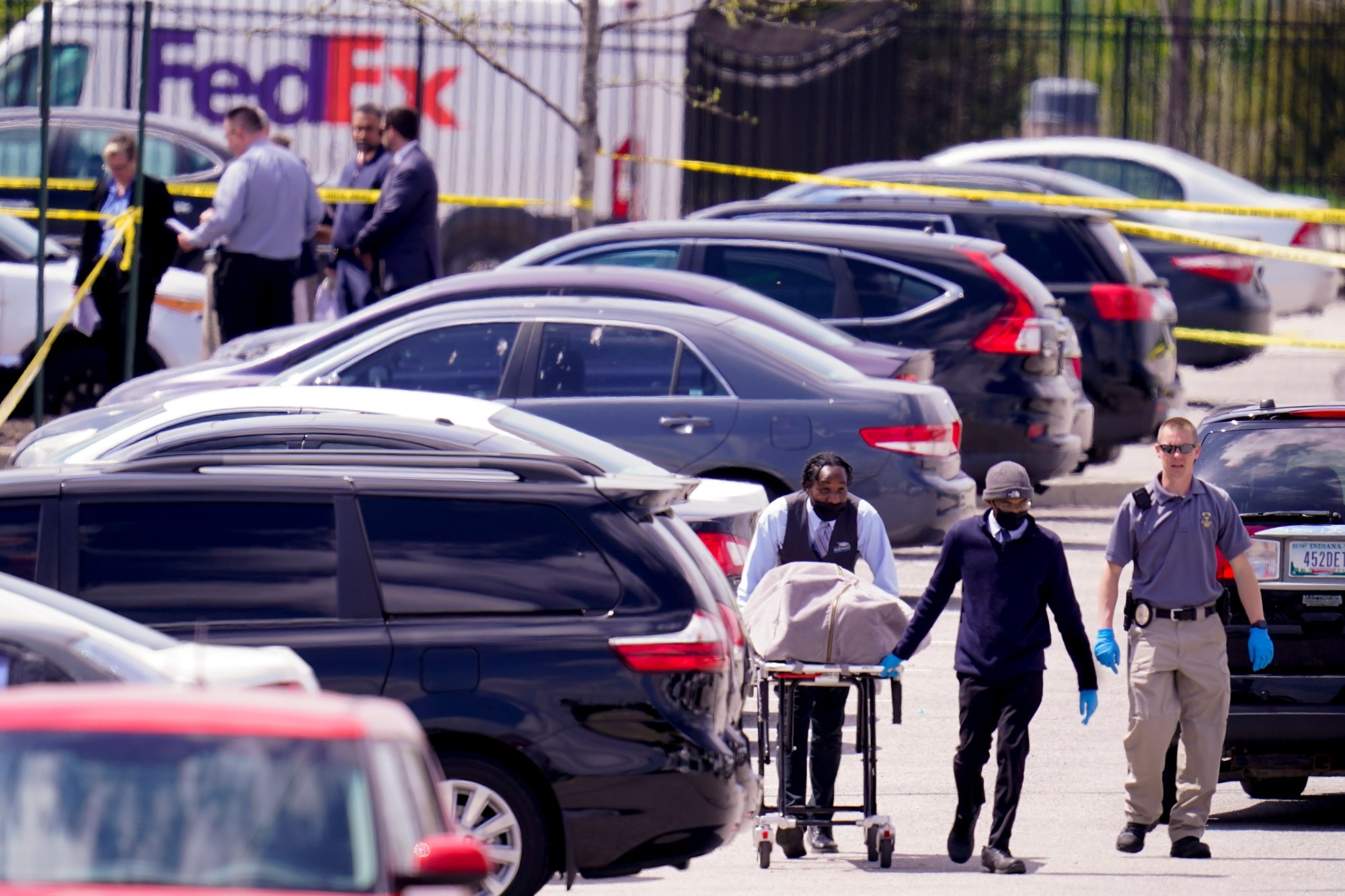 A body is taken from the scene where multiple people were shot at a FedEx Ground facility in Indianapolis, Friday, April 16, 2021. (AP Photo/Michael Conroy)