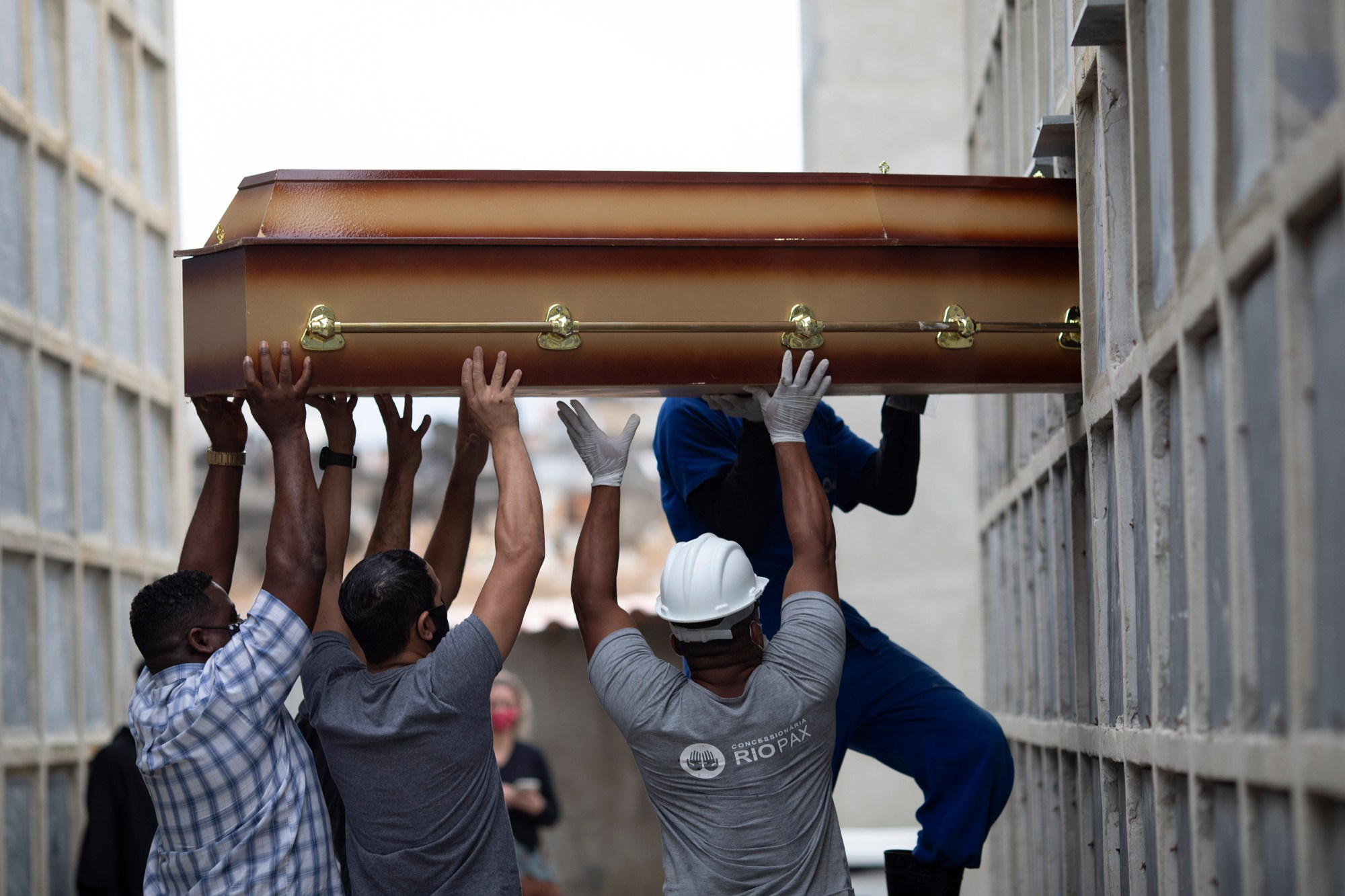 In this April 13, 2021, file photo, the remains of a woman who died from complications related to COVID-19 are placed into a niche by cemetery workers and relatives at the Inahuma cemetery in Rio de Janeiro, Brazil. (AP Photo/Silvia Izquierdo, File)