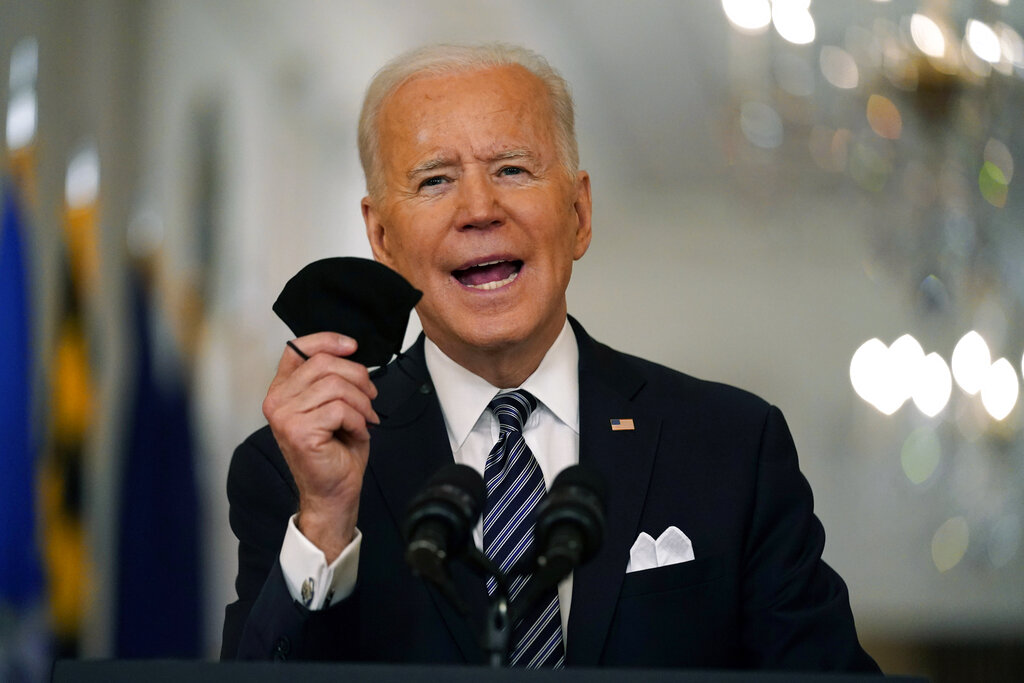In this March 11, 2021, file photo, President Joe Biden holds up his face mask as he speaks about the COVID-19 pandemic during a prime-time address from the East Room of the White House in Washington. (AP Photo/Andrew Harnik, File)