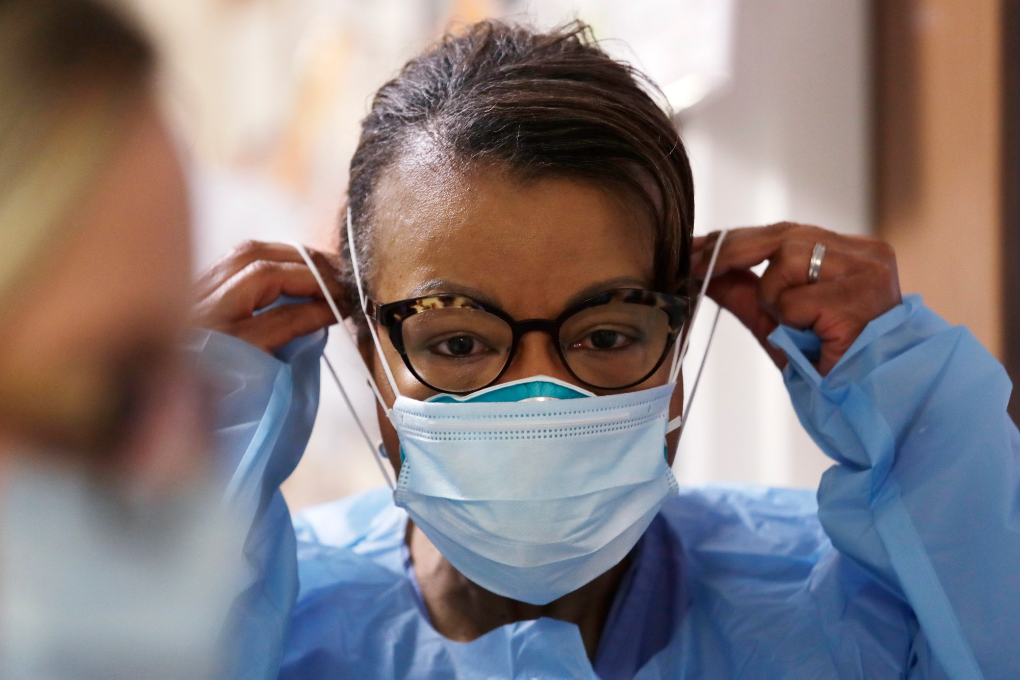 In this Friday, May 8, 2020 file photo, a respiratory therapist pulls on a second mask over her N95 mask before adding a face shield as she gets ready to go into a patient's room in the COVID-19 Intensive Care Unit at a hospital in Seattle. (AP Photo/Elaine Thompson)