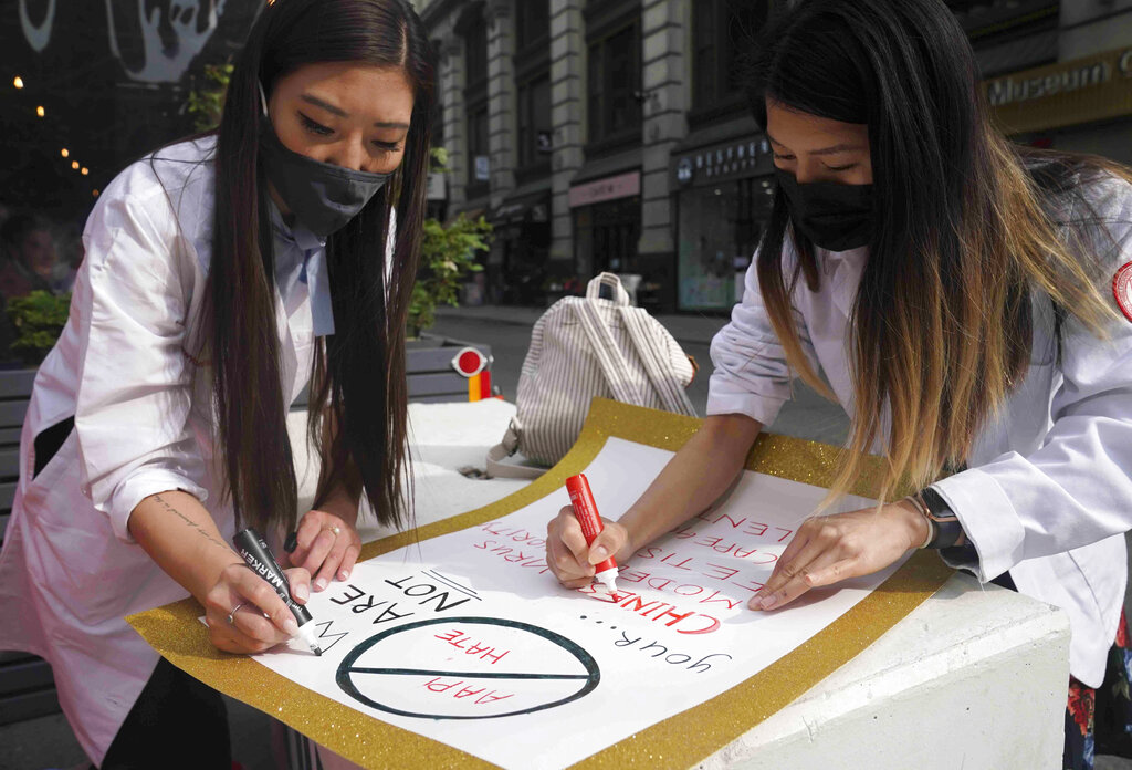 Dr. Michelle Lee, left, a radiology resident, and Ida Chen, right, a physician assistant student, prepare posters they carry at rallies protesting anti-Asian hate, Saturday April 24, 2021, in New York's Chinatown. (AP Photo/Bebeto Matthews)