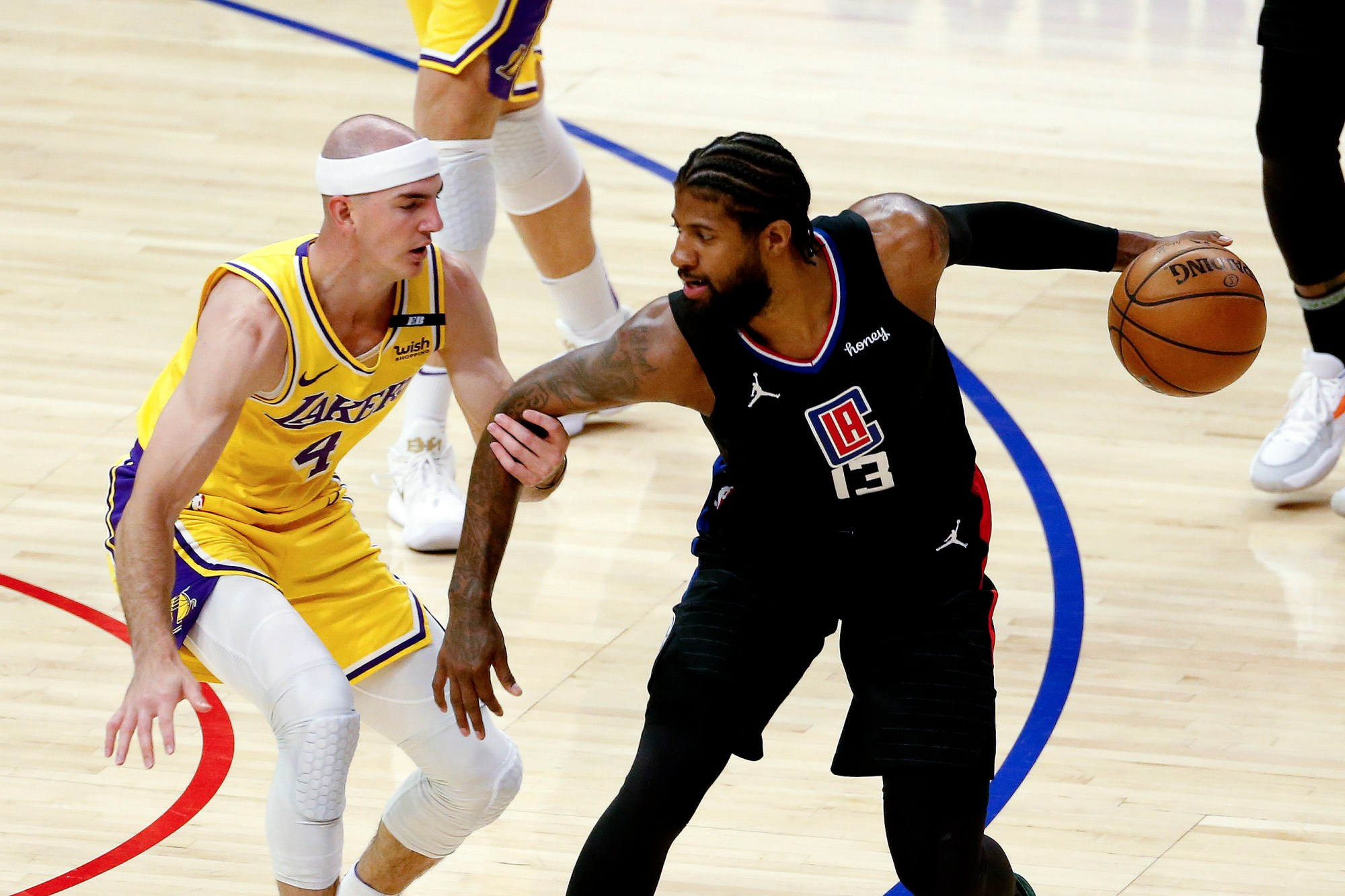 Los Angeles Clippers' Paul George is defended by Los Angeles Lakers' Alex Caruso during the first half of an NBA basketball game at the Staples Center on May 6, 2021. (Ringo H.W. Chiu / Associated Press)