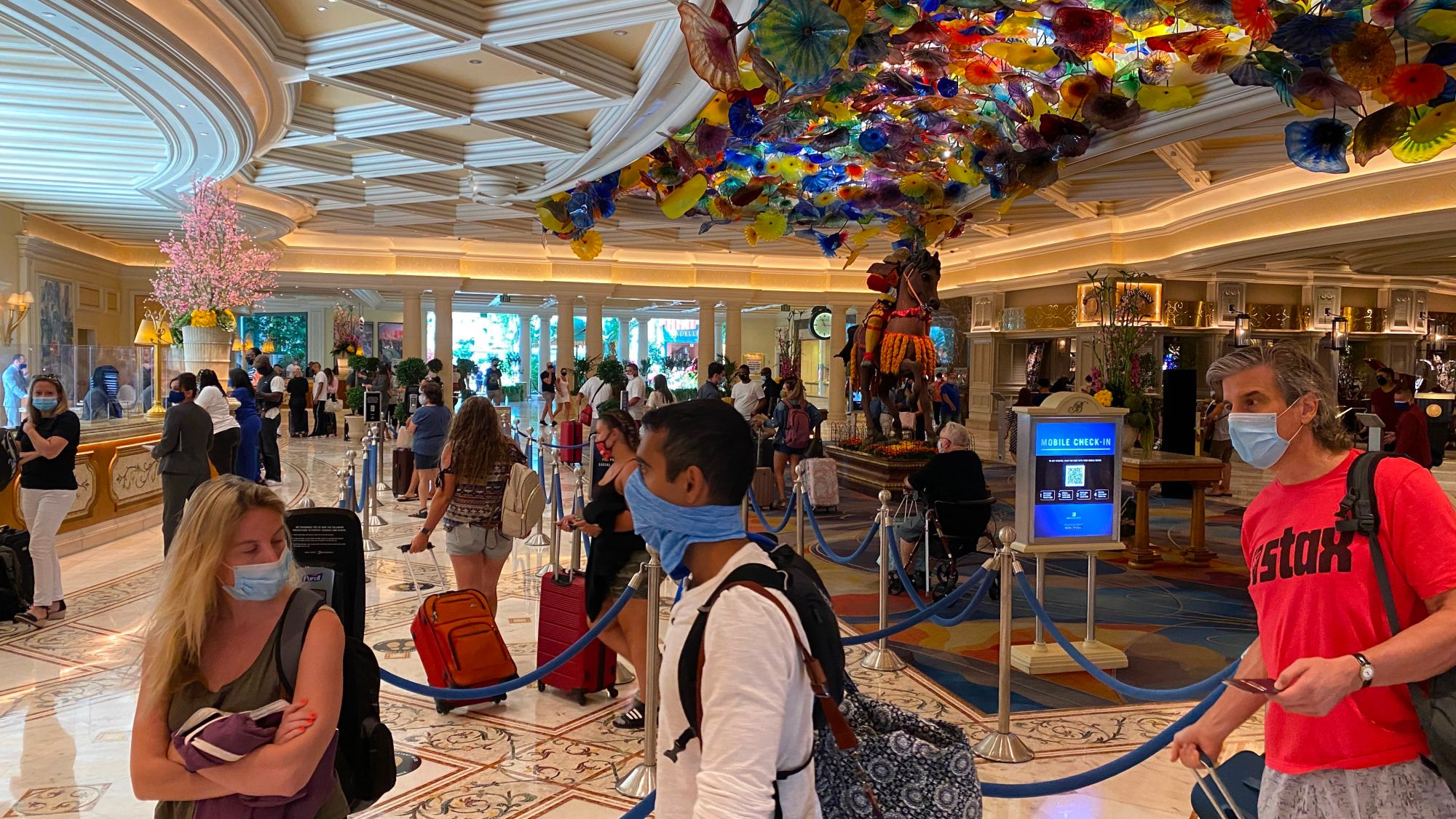 Tourists are wearing a mandatory mask as they wait to check-in at the Bellagio hotel and casino in Las Vegas, Nevada, on August 28, 2020 amid the coronavirus pandemic. (DANIEL SLIM/AFP via Getty Images)