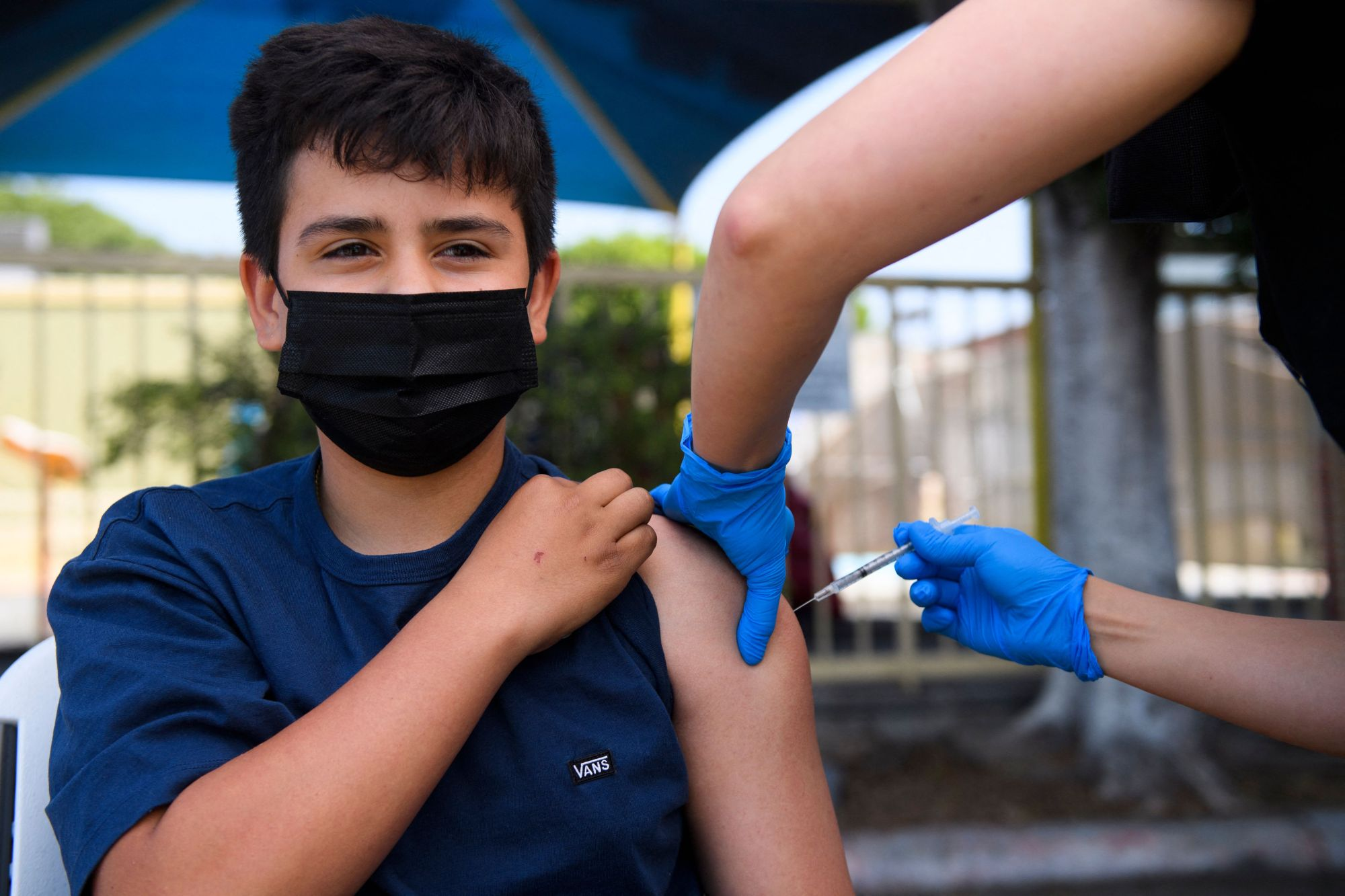 Simon Huizar, 13, receives a first dose of the Pfizer COVID-19 vaccine at a mobile vaccination clinic at the Weingart East Los Angeles YMCA on May 14, 2021, in Los Angeles.