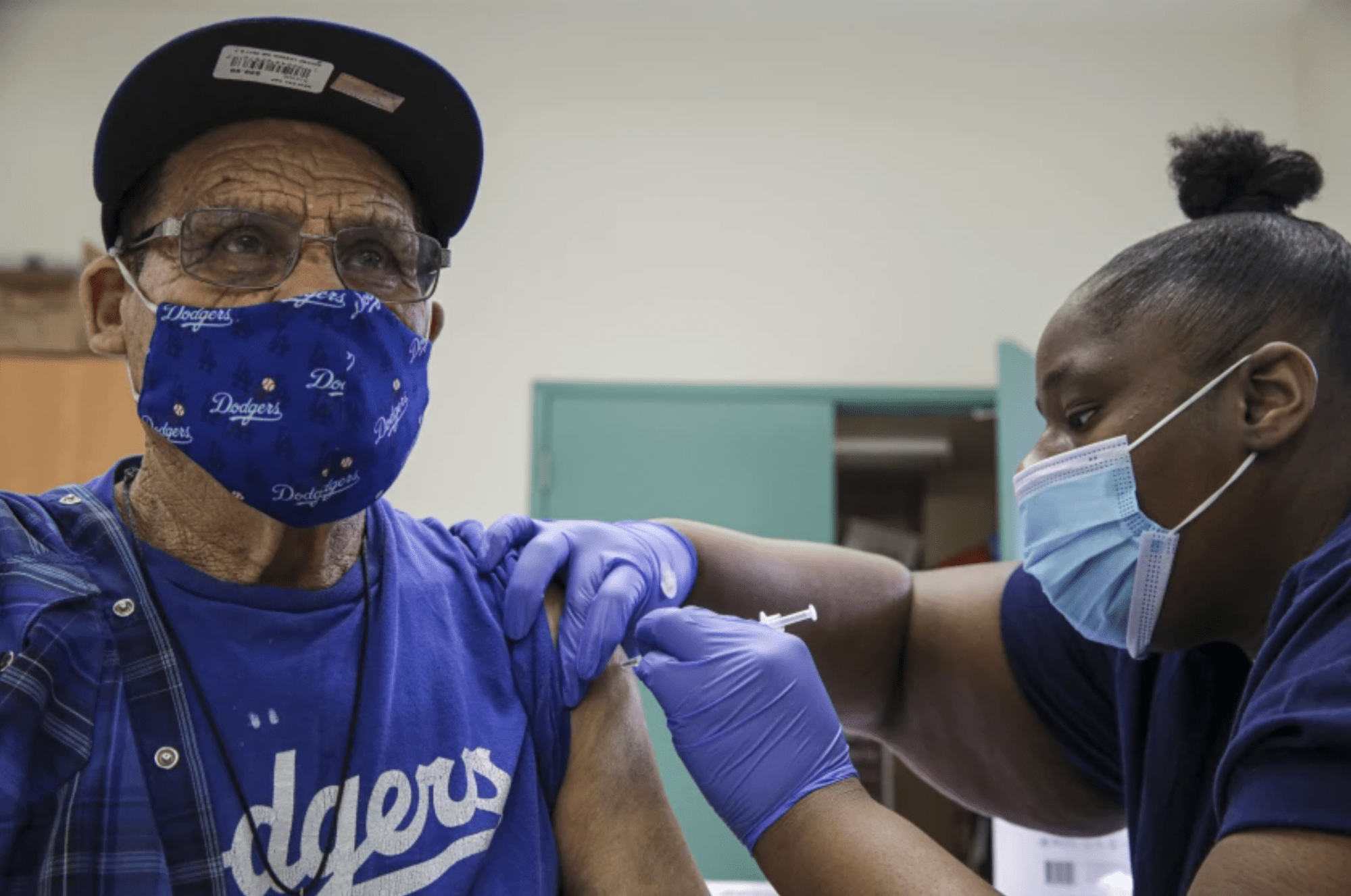 Jewel Morris, right, administers a Pfizer COVID-19 vaccine at mobile vaccine clinic at Roosevelt Park.(Irfan Khan / Los Angeles Times)