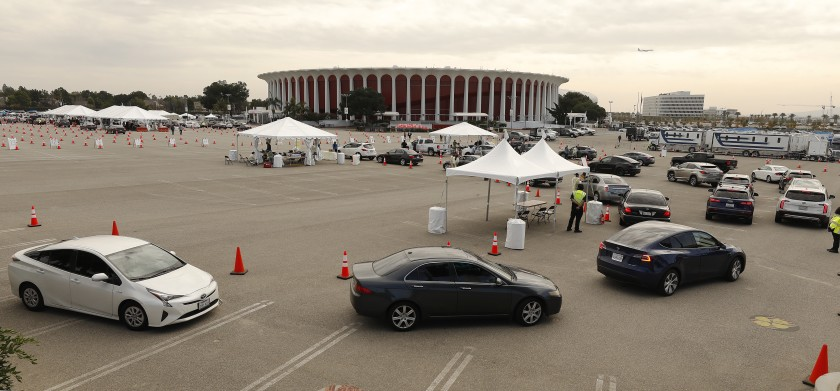 Vehicles line up at the Forum in Inglewood for vaccinations on Jan. 19. Orange County is closing its mass vaccination sites, though four sites in L.A. County will remain open for the foreseeable future.(Al Seib / Los Angeles Times)