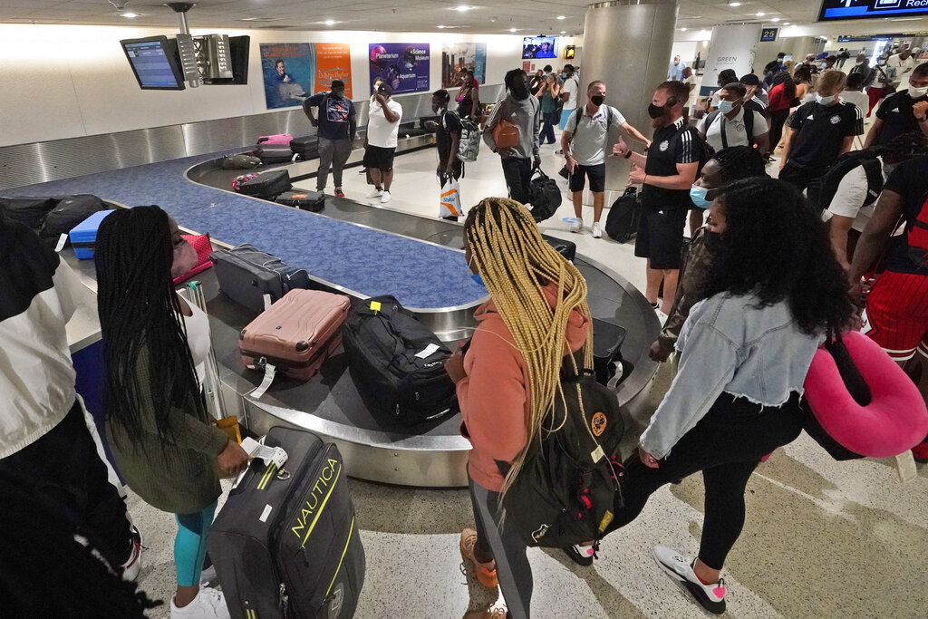 In this May 28, 2021 file photo, travelers wait for their luggage at a baggage carousel at Miami International Airport in Miami. (AP Photo/Wilfredo Lee, File)