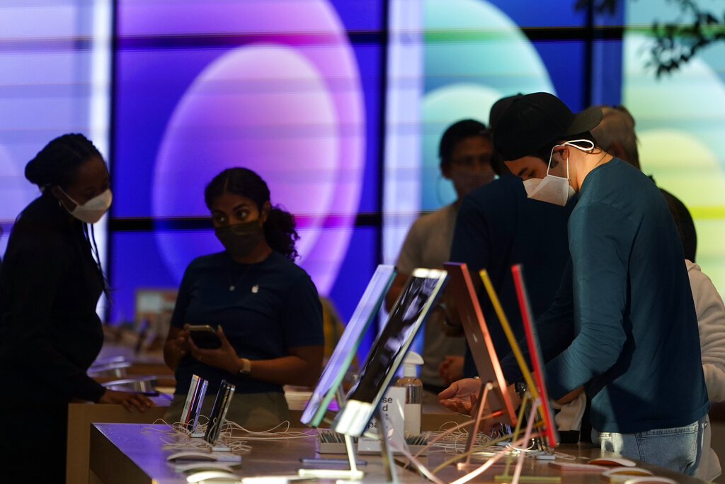 In this June 9, 2021, file photo, workers and customers wear masks inside an Apple Store amid the COVID-19 pandemic on The Promenade, in Santa Monica, Calif. (AP Photo/Marcio Jose Sanchez, File)