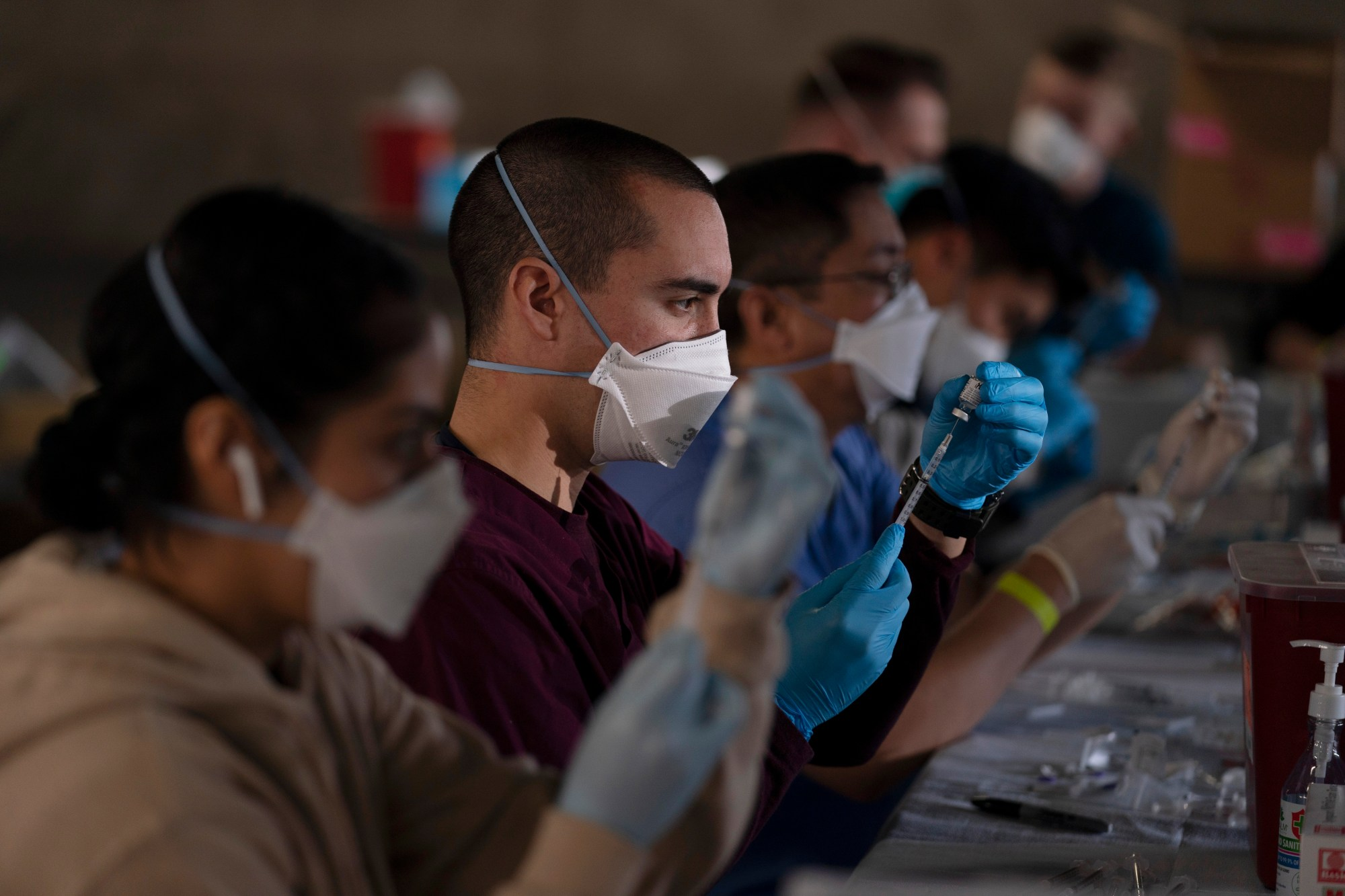 Members of the California National Guard fill syringes with Pfizer's COVID-19 vaccine at a site in Long Beach on March 5, 2021. (Jae C. Hong / Associated Press)