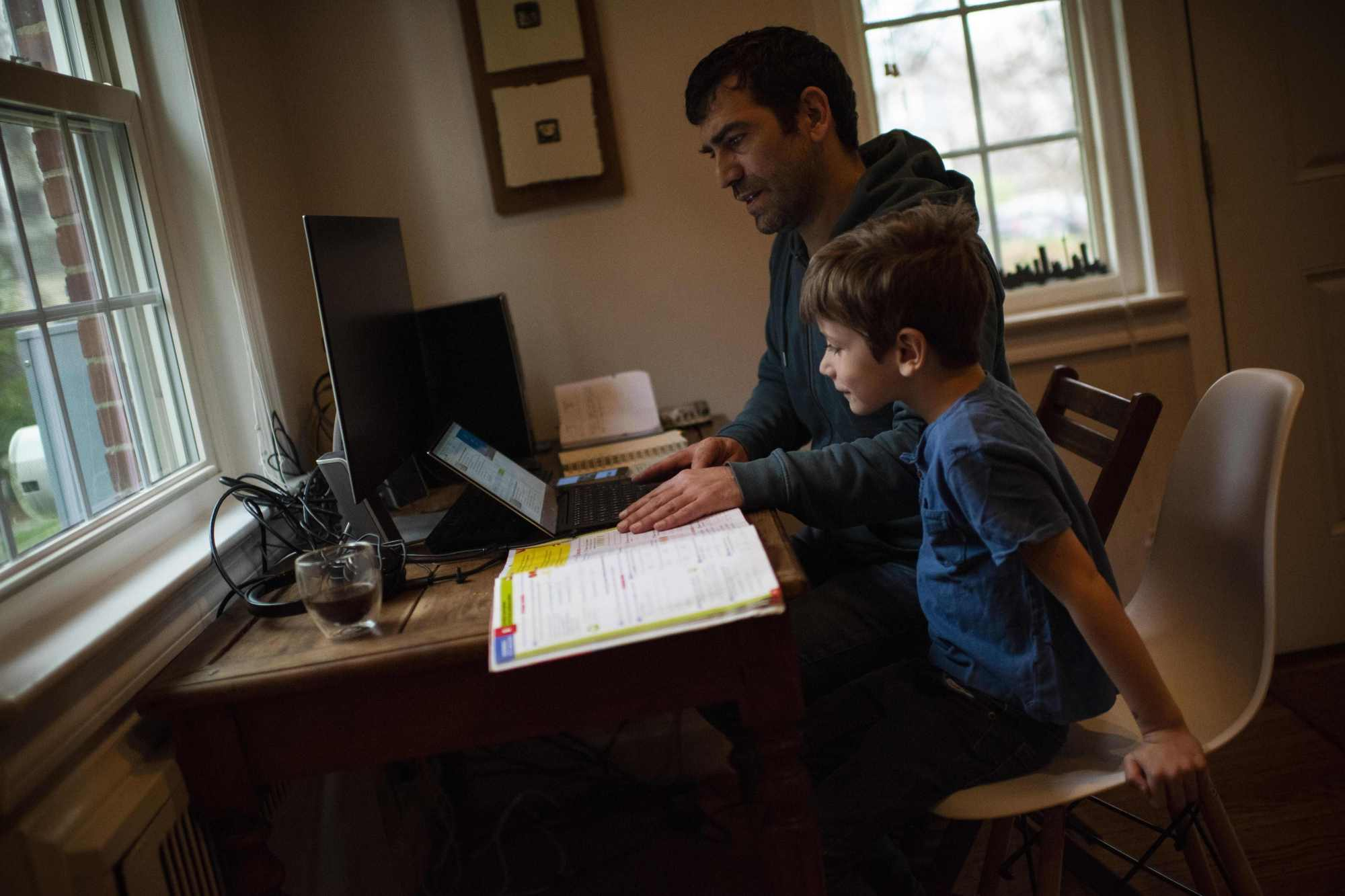 Joachim, 8, whose school was closed following the Coronavirus outbreak, does school exercises at home with his dad Pierre-Yves in Washington on March 20, 2020. (Eric Baradat/AFP via Getty Images)