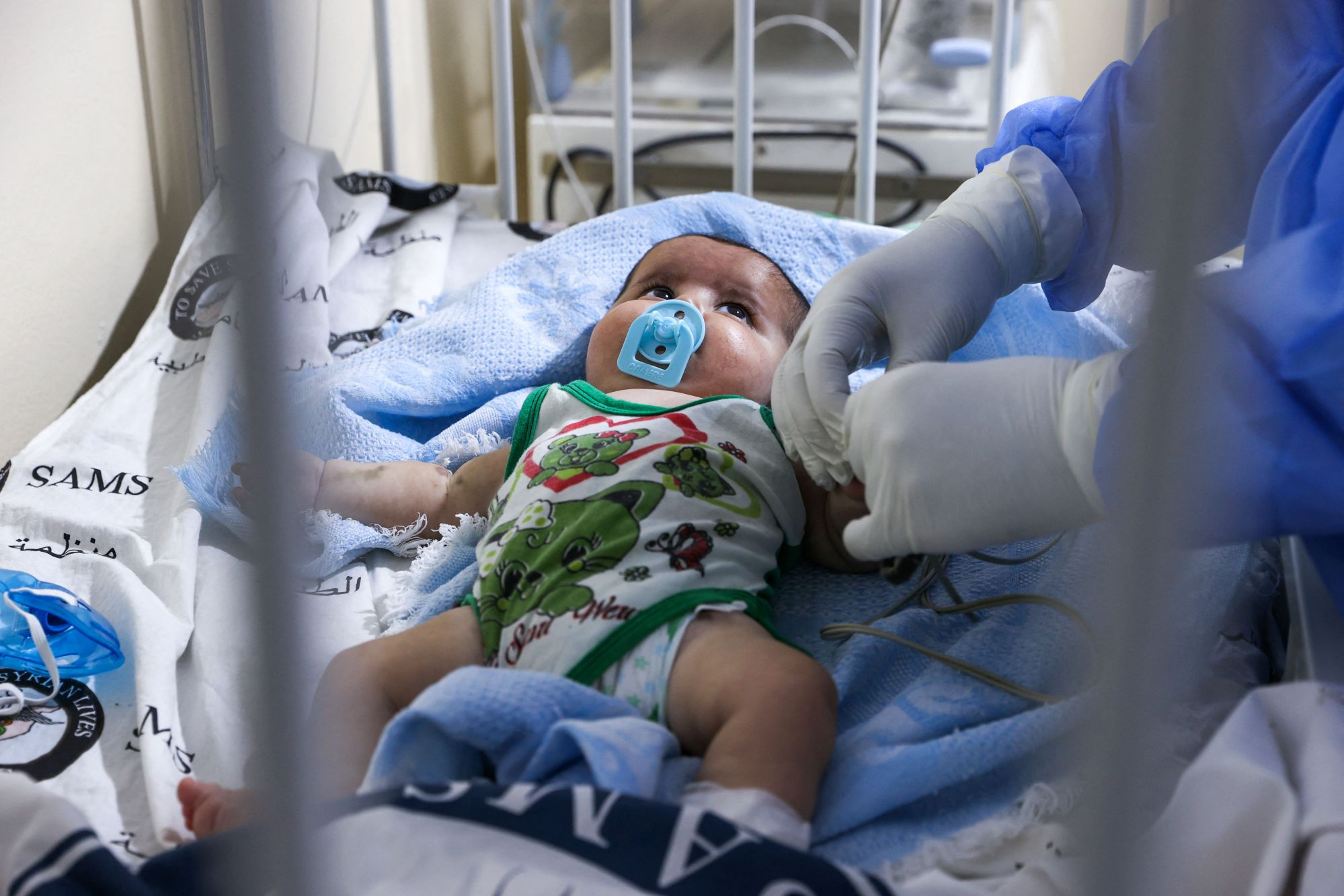 A medic cares for a baby at a COVID-19 isolation ward, in Syria, on Sept. 5, 2021. (OMAR HAJ KADOUR/AFP via Getty Images)