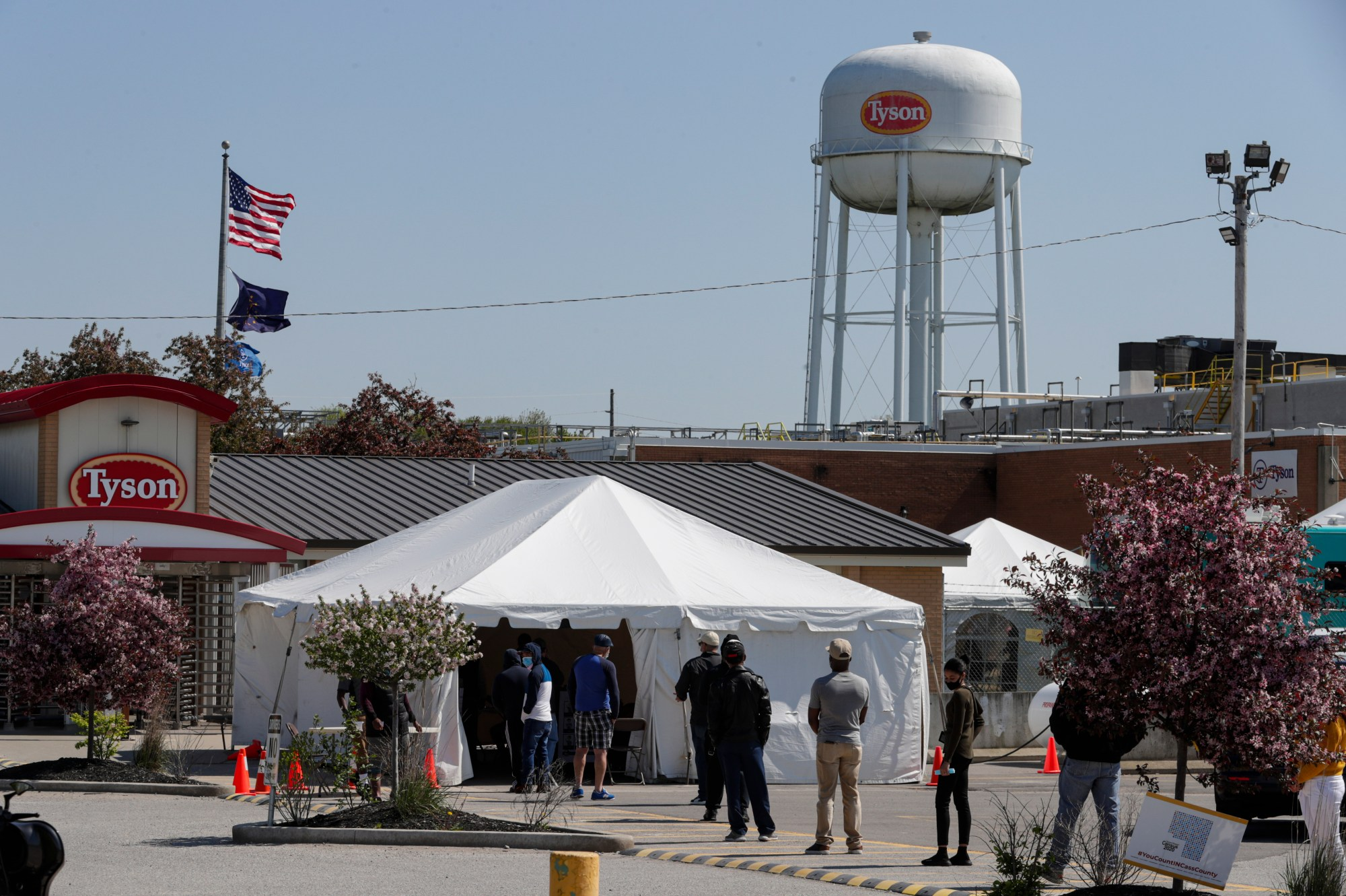 In this May 7, 2020, file photo workers wait in line to enter the Tyson Foods pork processing plant in Logansport, Ind. At least 59,000 meatpacking workers became ill with COVID-19 and 269 workers died when the virus tore through the industry last year, which is significantly more than previously thought, according to a new U.S. House report released Wednesday, Oct. 27, 2021. (AP Photo/Michael Conroy, File)