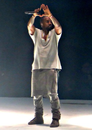 Kanye West holding up his hands making a triangle shape to the crowd during his performance