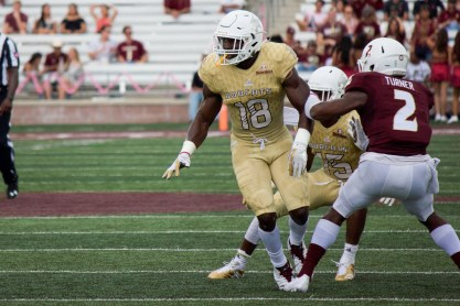 In a bright golden jersey, linebacker Frankie Griffin takes an aggressive step-forward against the night black jerseys of the University of Louisiana-Monroe.