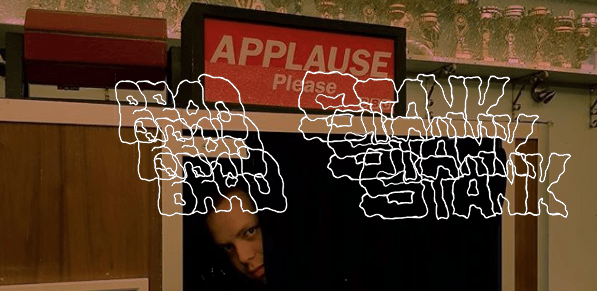 """Brad Stank poses for a photograph underneath a sign that reads """"Applause Please."""" The words """"Brad Stank"""" appear in triplicate in the foreground of the picture."""
