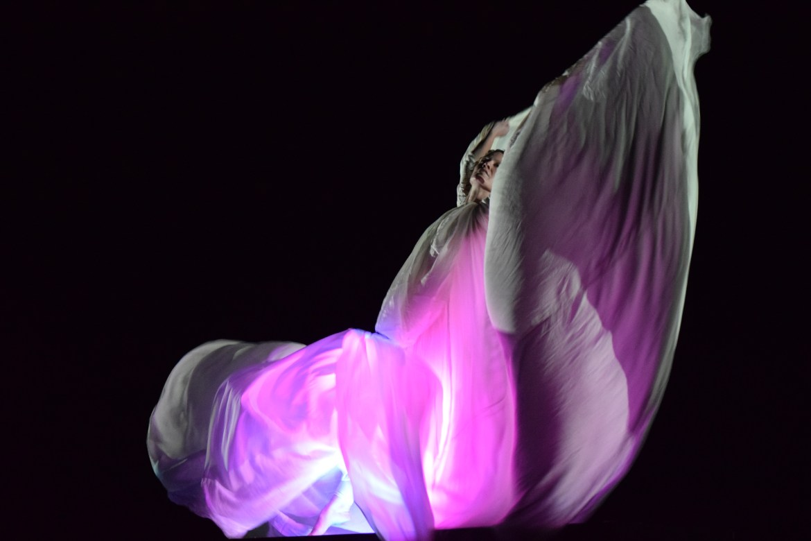 Jessica Lindberg Coxe dressed in a flowy white dress dances as purples and pinks are projected onto the fabric.