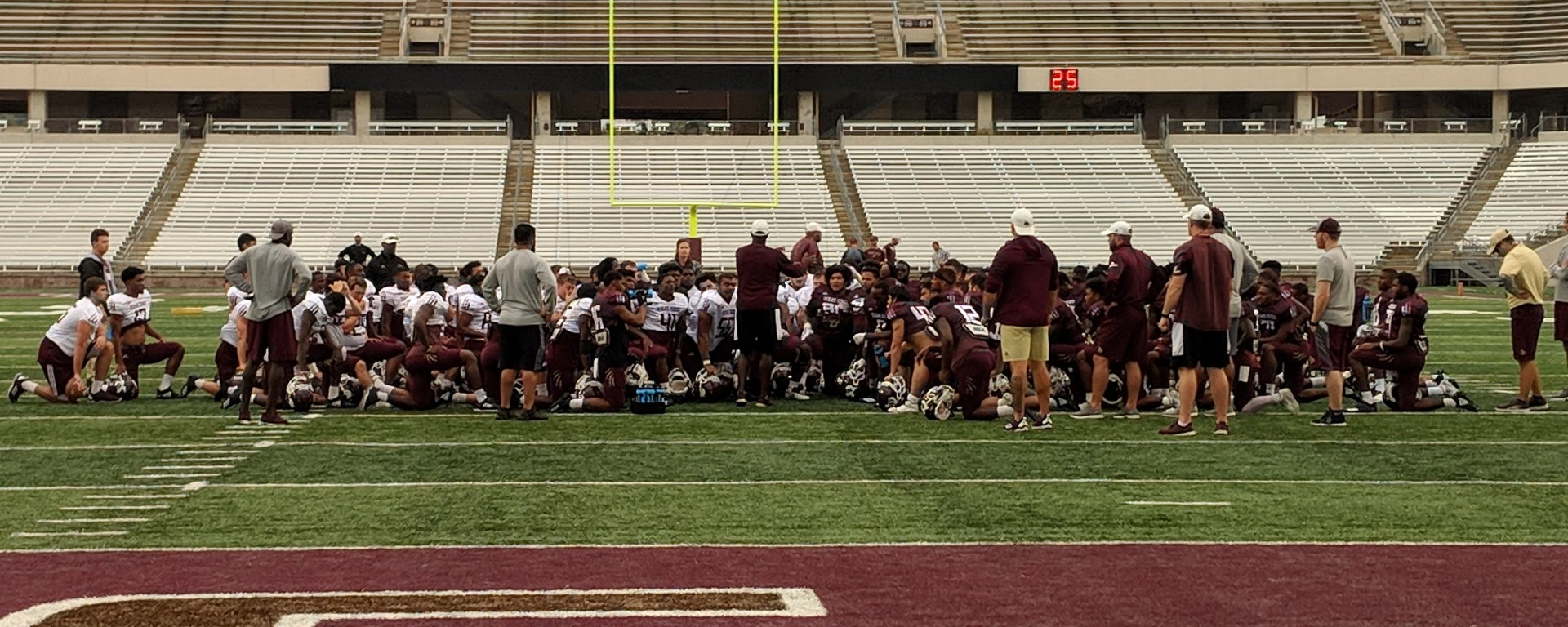 After warmups during a cloudy, September practice, the Texas State Bobcats gather at the 20-yard line of Bobcat Stadium as Coach Withers addresses them.