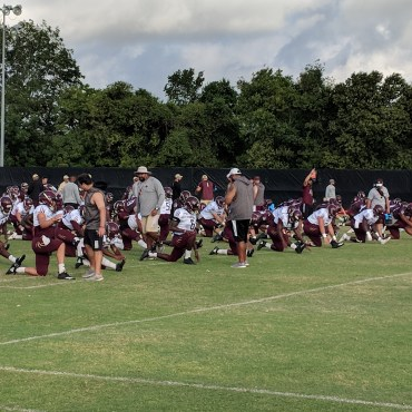 Bobcat football players stretching on the practice field.