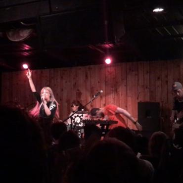 A blonde woman and a band performing a high-energy show.