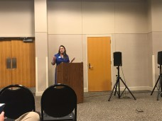 Erin Zwiener standing behind a podium talking to audience during a town hall