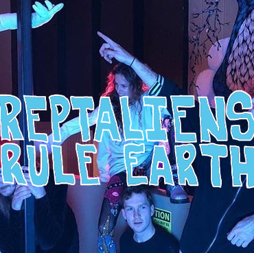 The members of Reptaliens pose for a group photo under pale blue lights. The band is accompanied by one of their onstage creatures, this one wearing a plastic mask with red cheeks and abnormally long arms.