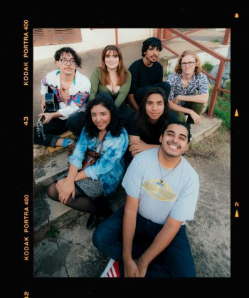 The five band members of Wezmer along with two from their team sitting together on a set of stairs and posing for the camera, the member furthest left is playing a black acoustic guitar. There are film camera strips along the left and right borders of the photo.